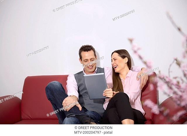 Young couple sitting sofa laughing tablet computer