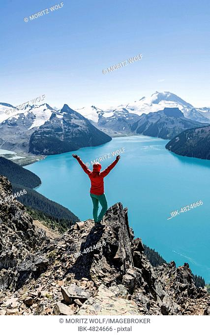 View from Panorama Ridge Hiking Trail, Hiker on a rock stretches arms into the air, Garibaldi Lake, Turquoise Glacial Lake, Guard Mountain and Deception Peak