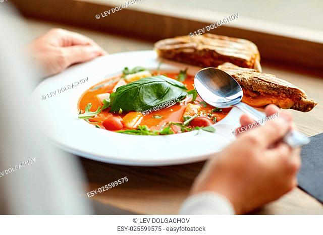 food, dinner, culinary and people concept - woman eating gazpacho soup with sandwich and spoon at restaurant
