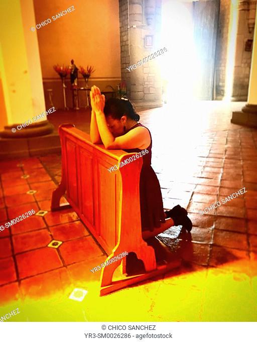 A Mexican woman prays in a church in Cholula, Mexico