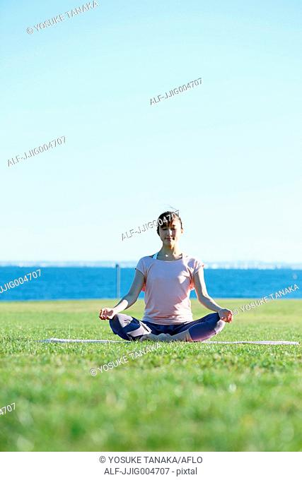 Young Japanese woman practicing yoga in a city park