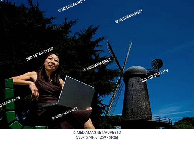 Low angle view of a mature woman sitting on a bench with a laptop on her lap, Golden Gate Park, San Francisco, California, USA