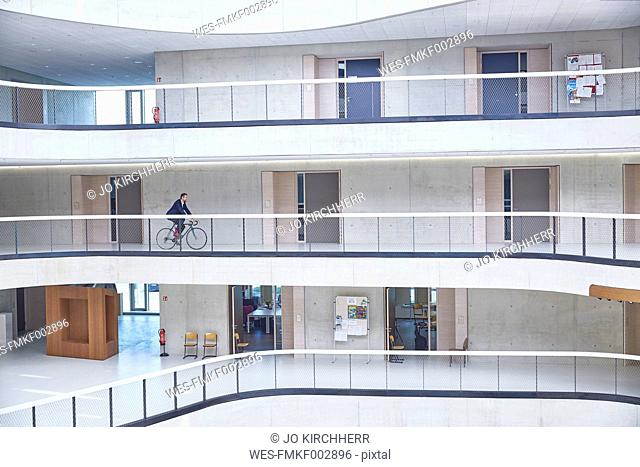 Businesssman riding bicycle in modern office building