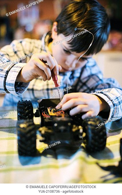 Child fixing his toy car, using a screwdriver