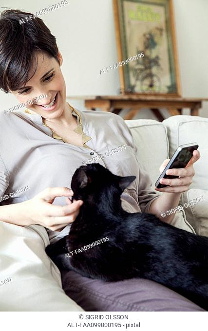 Woman sitting on sofa with cat on her lap