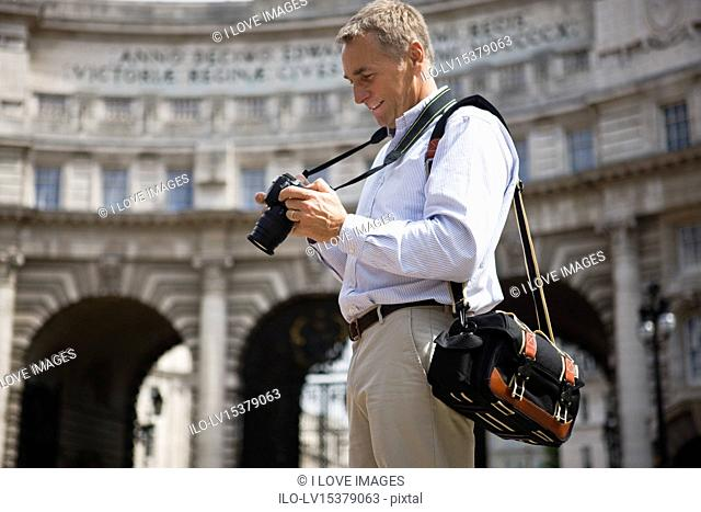 A middle-aged man standing by Admiralty Arch, looking at his camera