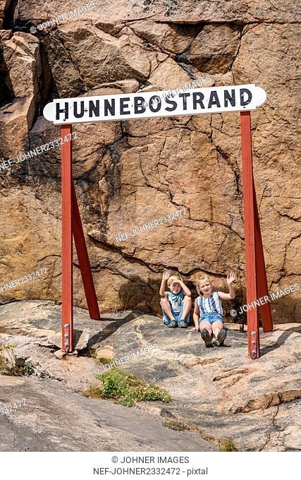 Children sitting under sign, Hunnebostrand, Gotaland, Sweden