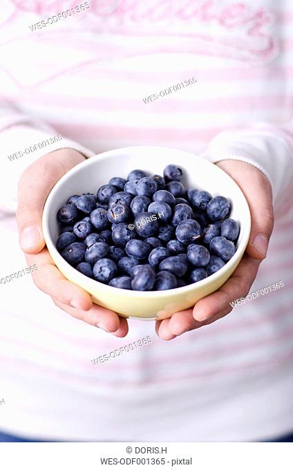 Woman's hands holding bowl of blueberries