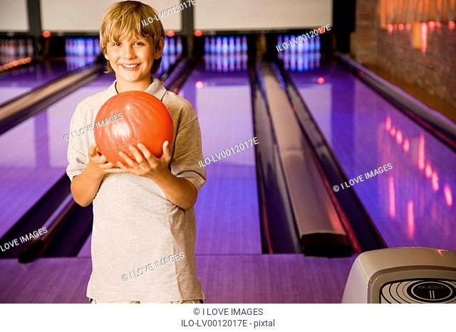 Boy in a bowling alley holding a red bowling ball