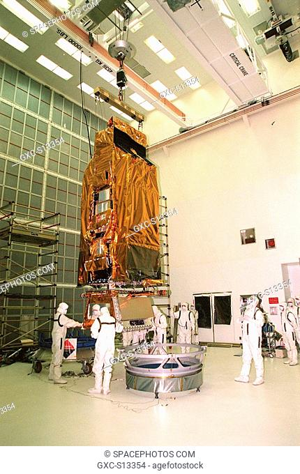 05/04/1999 --- While a crane lifts NASA's Far Ultraviolet Spectroscopic Explorer FUSE satellite, workers at Hangar AE, Cape Canaveral Air Station