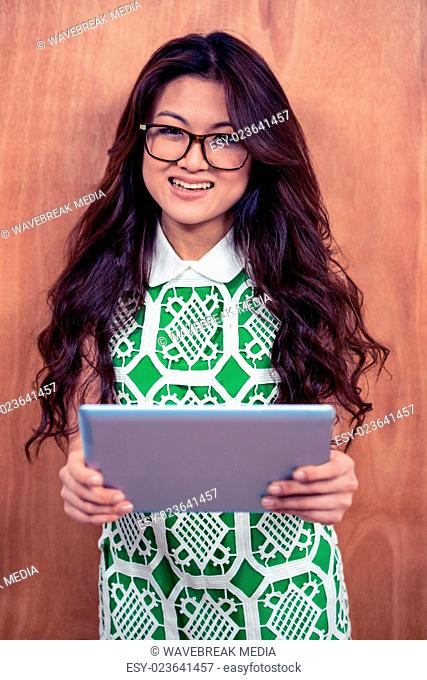 Smiling Asian woman holding tablet and looking at the camera