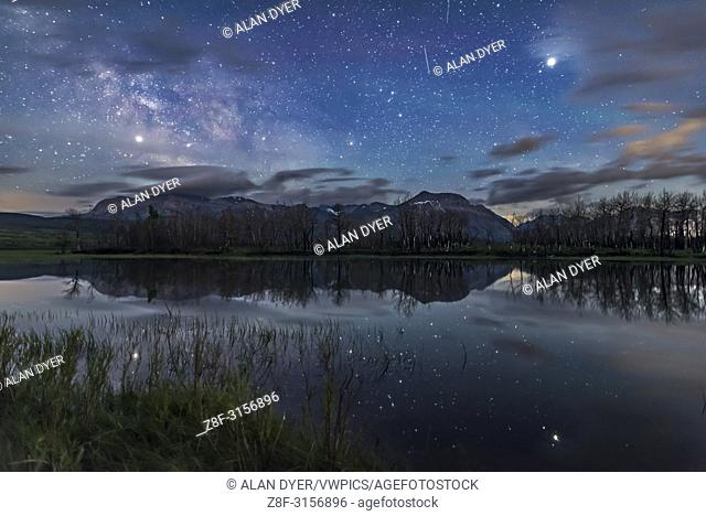 Jupiter (at right) and Saturn (at left) shining brightly in the sky and reflected in the still waters of Maskinonge Lake at Waterton Lakes National Park