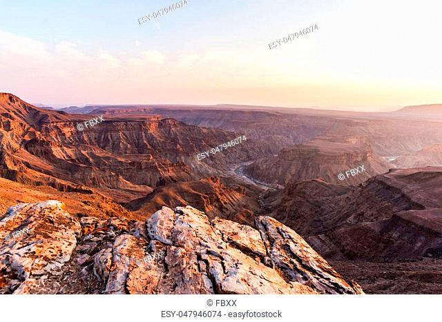 Fish River Canyon, scenic travel destination in Southern Namibia. Last sunlight on the mountain ridges. Wide angle view from above
