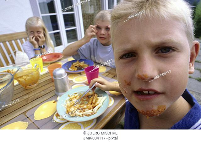 Three children, two boys and a girl, 5-10 years old, sitting on a terrace in front of a house, having lunch