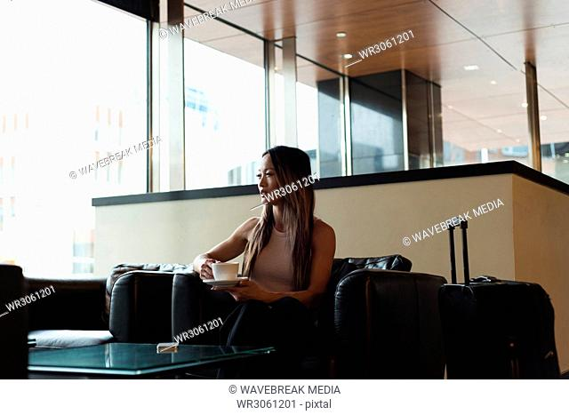 Businesswoman sitting alone looking away while having coffee