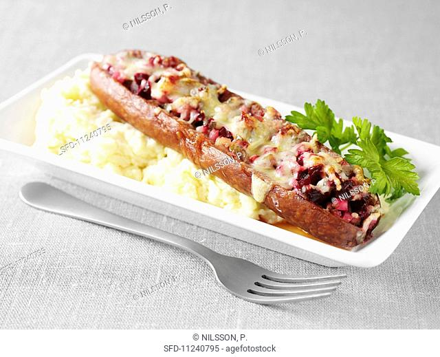 Stuffed air-cured sausage topped with cheese and baked, on a bed of mashed potato