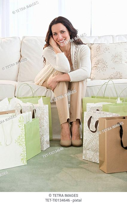 Portrait of woman sitting on sofa with shopping bags