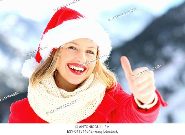 7a3336b975974 Front view portrait of a woman wearing santa claus hat on christmas  holidays with thumbs up