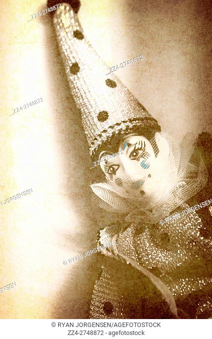 Close up on head and tall cone shaped hat of smiling clown doll with smile as old postcard or sepia tone