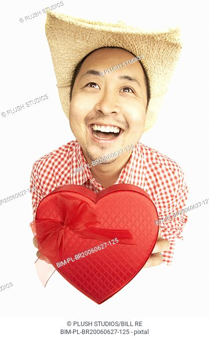 Asian man wearing cowboy hat and holding heart box