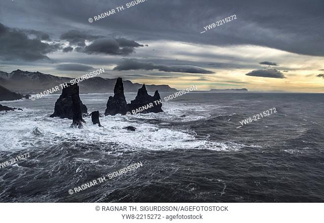 Basalt Sea Stacks and waves at Reynisfjara Beach located by Vik in Myrdal, South Coast of Iceland. Icelandic folklore states that these stacks are thought to be...