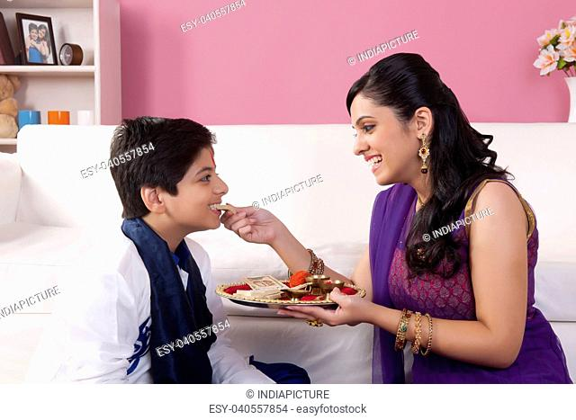 Sister feeding sweets to her brother at Bhaidooj