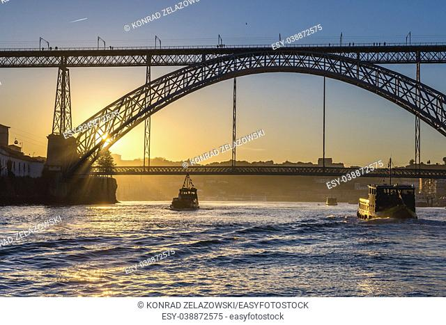Tourist boats and Dom Luis I Bridge over Douro River between Porto and Vila Nova de Gaia cities in Portugal