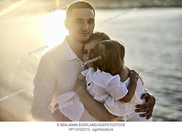 family at seaside, at sunset, one child. In Chersonissos, Crete, Greece