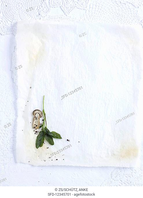 Sage leaves, ground pepper, and a mushroom on a white background