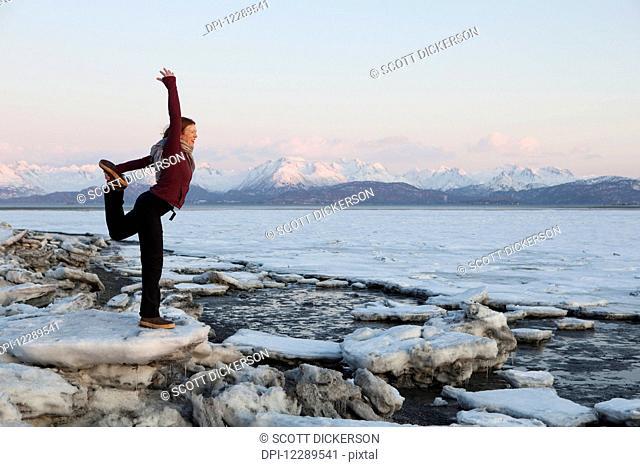 Woman practices yoga on an ice chunk on a beach in Homer, Southcentral Alaska