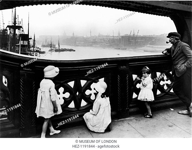 People watching the Thames from Tower Bridge, City of London, c1930. A man smoking a pipe and some little girls stand by an ironwork balustrade on Tower Bridge