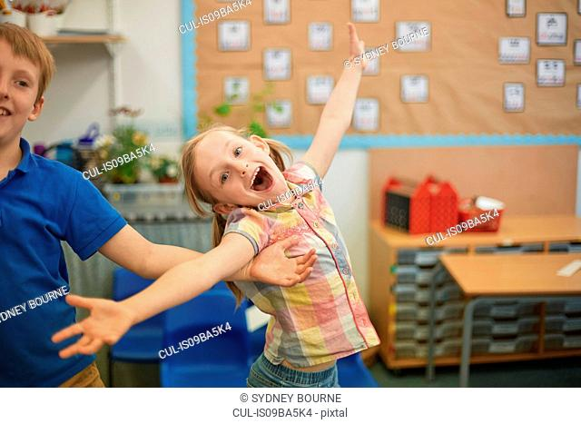 Primary schoolgirl and boy fooling around in classroom