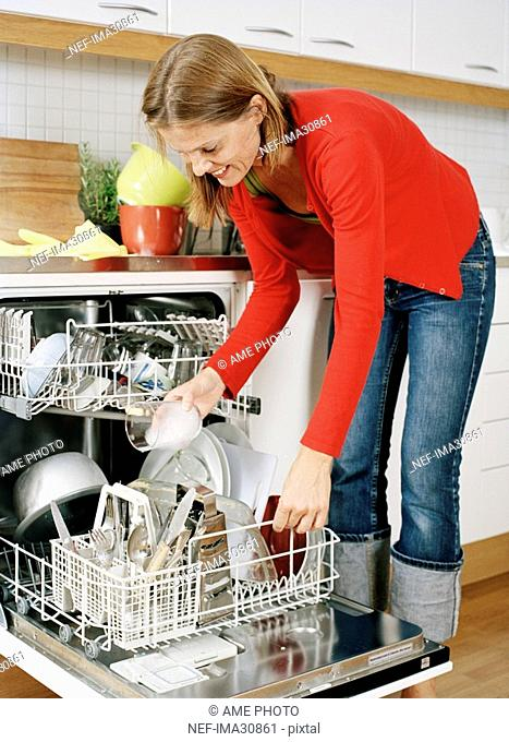 A woman putting dishes in a dishwasher