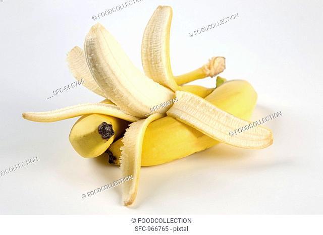 Three bananas, one half-peeled