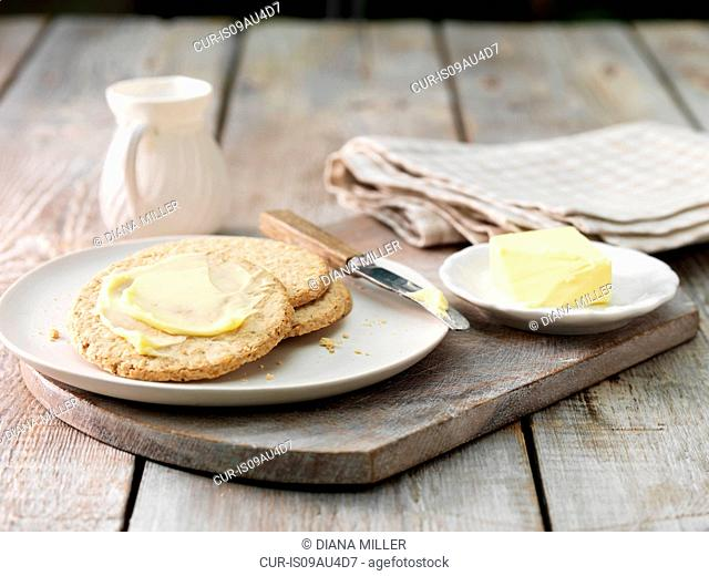 Oat crackers smeared with butter, butter dish and butter knife on aged wood surface