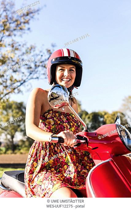 Portrait of happy young woman on motor scooter