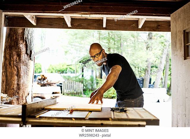 Man wearing glasses working in a lumber yard