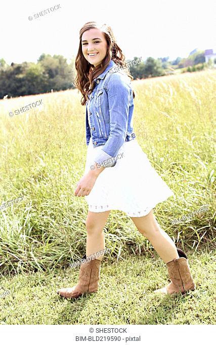 Woman walking in tall grass in field