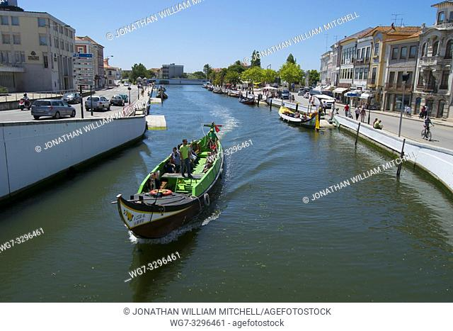 AVEIRO, PORTUGAL - June 28, 2016: Tourists enjoy a guided boat tour in a traditional Moliceiro boats in Aveiro, Portugal