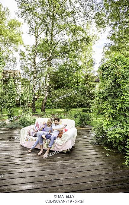 High angle view of couple sitting on vintage sofa in garden using digital tablet