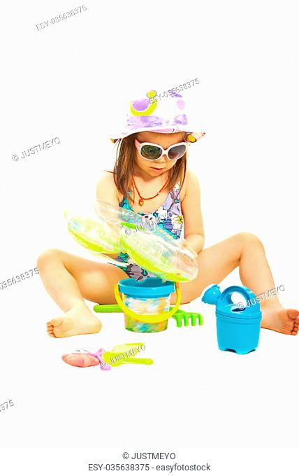 Girl sitting and playing with beach toys isolated on white background