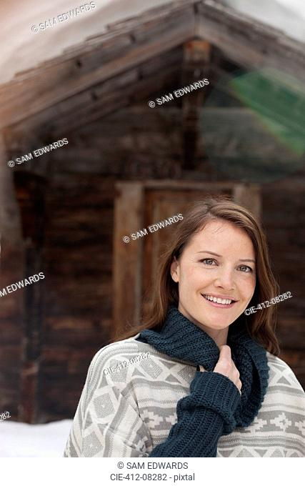 Portrait of smiling woman in snow outside cabin