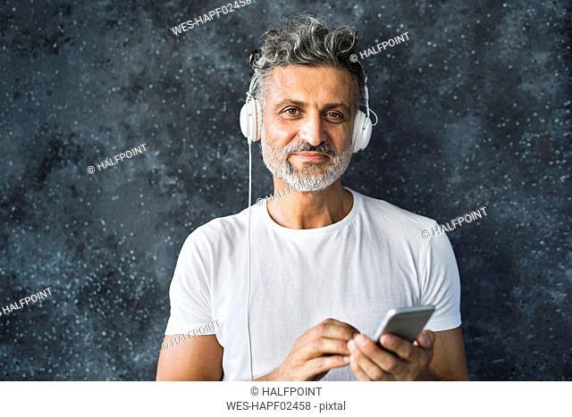 Portrait of a mature man using smartphone, wearing headphones