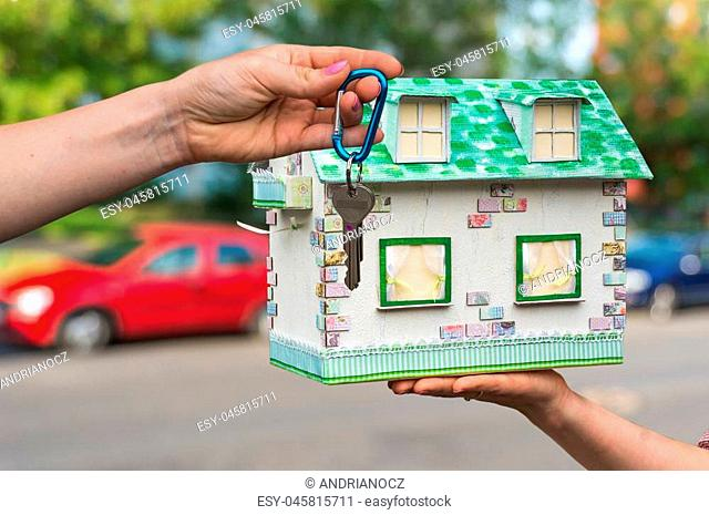Real estate agent giving house keys to a new property owner, who is holding model house from paper on blurred background