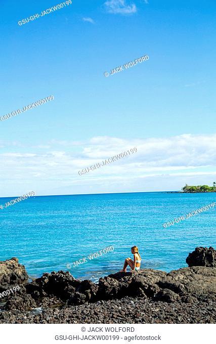 Young Girl Sitting on Lava Rocks near Pacific Ocean, Hawaii, USA