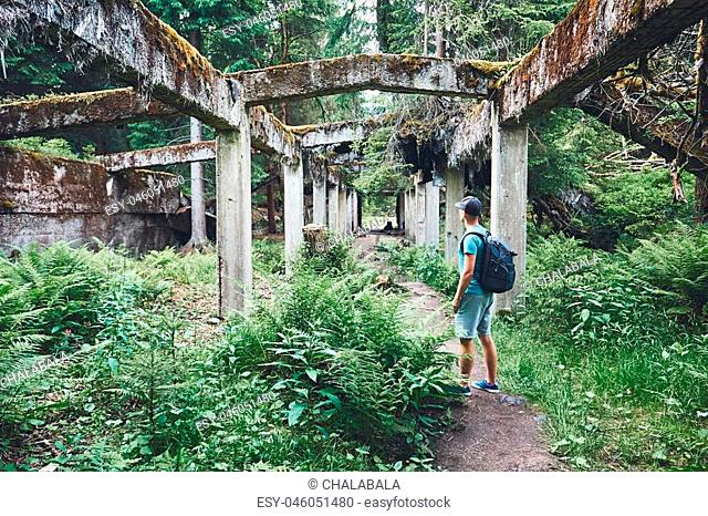 Young explorer inside of the abandoned old ruined factory in the middle of the forest. Ore mountains, Czech Republic