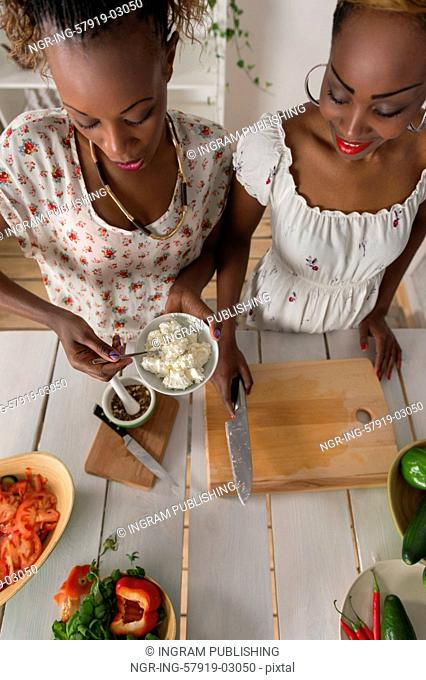 Two african women cooking in kitchen making healthy food salad with vegetables. Top view