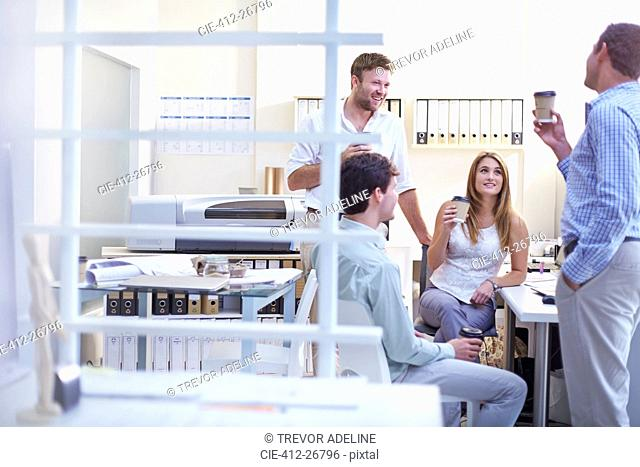 Architects talking and drinking coffee in office