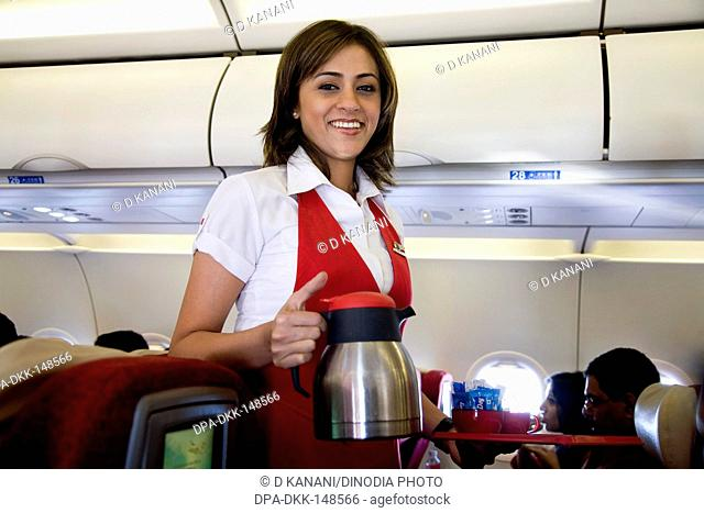Cabin crew serving tea coffee to passengers seating in kingfisher deccan flight air bus A320 at Chattrapati Shivaji Terminal ; Bombay now Mumbai ; Maharashtra ;...