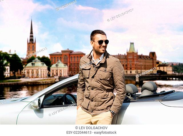 travel, tourism, road trip, transport and people concept - happy man near cabriolet car over city of stockholm in sweden background